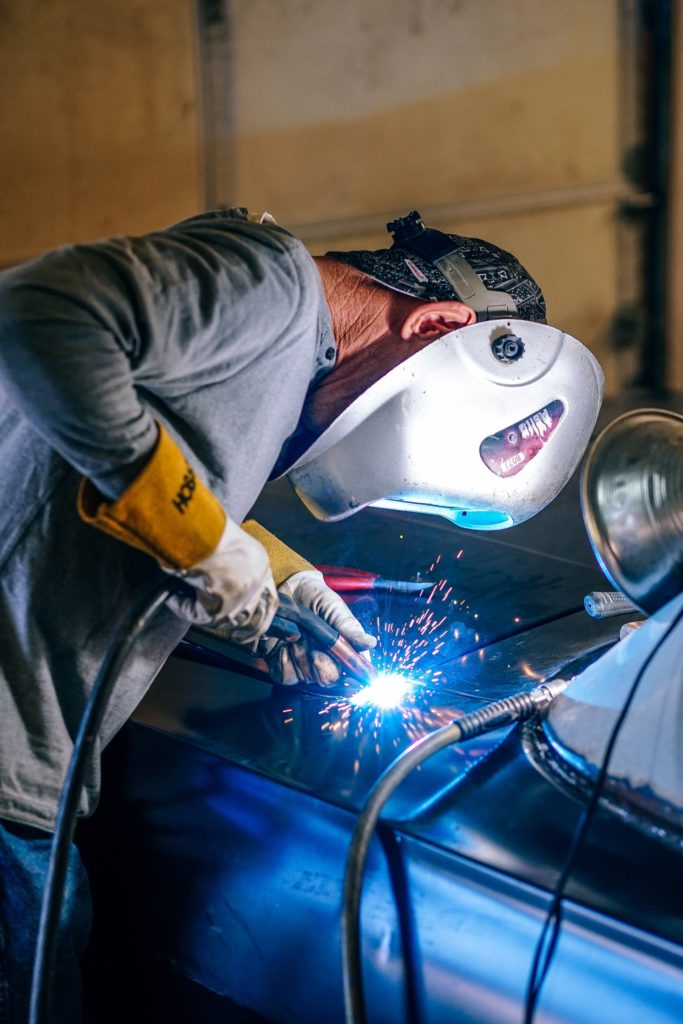 Welder working on a car